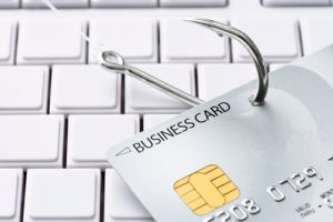 close up of credit card with fish hook going through it on top of computer keyboard