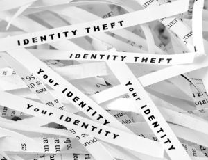 shredded paper strips that say identity theft and your identity