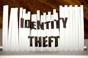 Vertical strips of paper forming the words IDENTITY-THEFT
